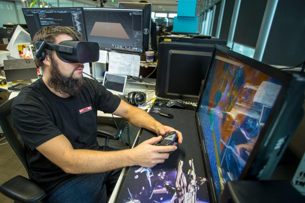 An Image of a Man with virtual reality glasses and playing video game.