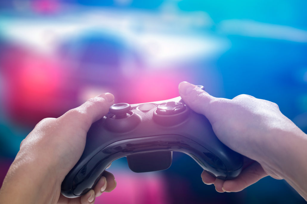 A Man holding the gaming gear in a blur background.